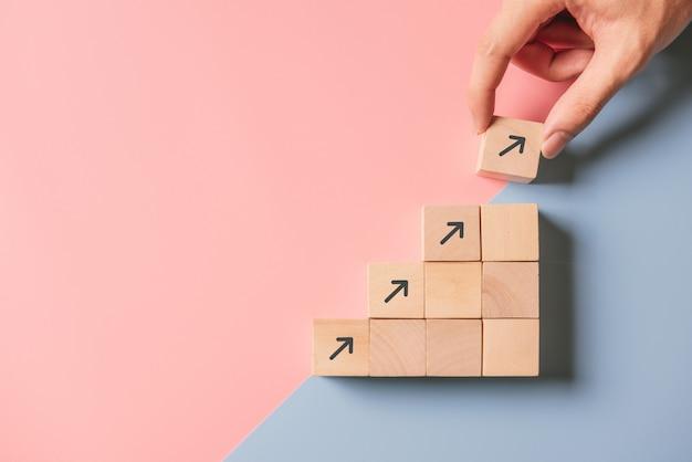 Processo di successo di crescita del concetto aziendale. chiuda sulla mano dell'uomo che sistema l'impilamento del blocco di legno come scala di punto sull'azzurro e sul rosa di carta Foto Premium