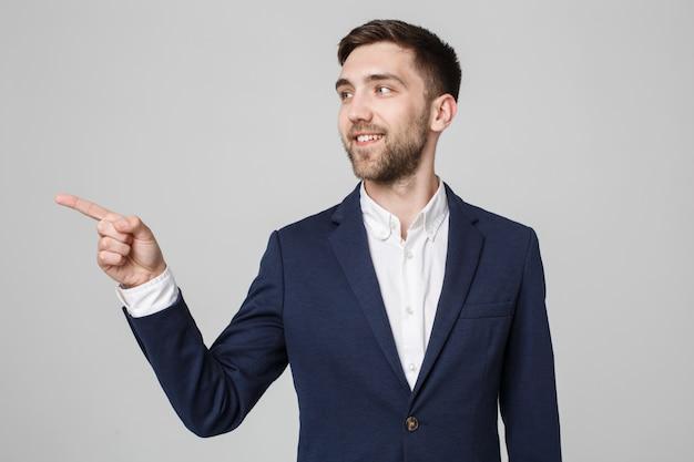 Concetto di business - ritratto bello uomo d'affari fiducia sorridente che punta con il dito. sfondo bianco. Foto Premium
