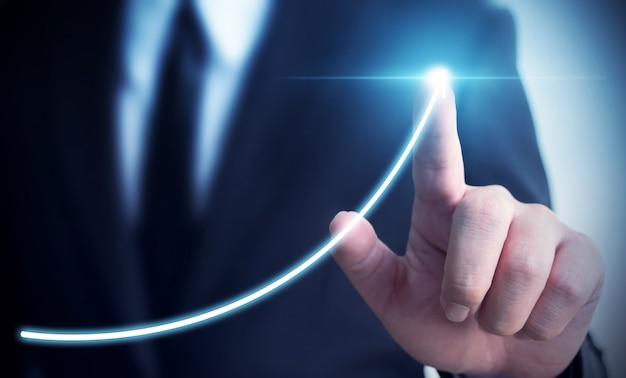 Sviluppo del business verso il successo e crescente concetto di crescita delle entrate annuali, uomo d'affari che indica il piano di crescita aziendale futuro grafico freccia Foto Premium