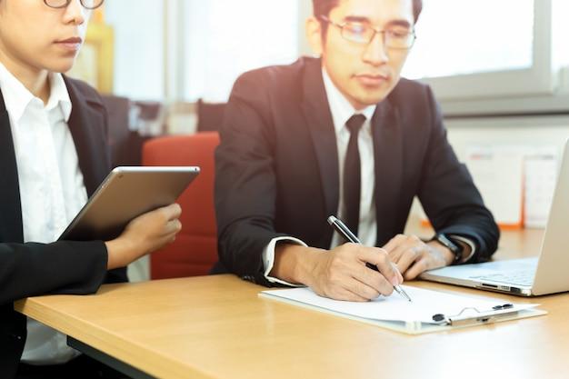 Contratti di firma dell'uomo d'affari con segretario allo scrittorio in ufficio. Foto Premium