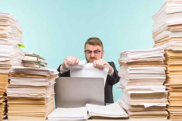 Dirigente aziendale che lavora in ufficio e pile di scartoffie Foto Premium