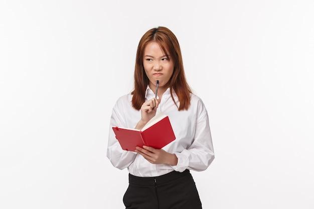 Concetto di business, finanza e carriera. ritratto di donna asiatica riluttante e infastidita in camicia, fare smorfie infastiditi, pensare, non piace preparare il progetto, mordere la penna e tenere il quaderno Foto Premium