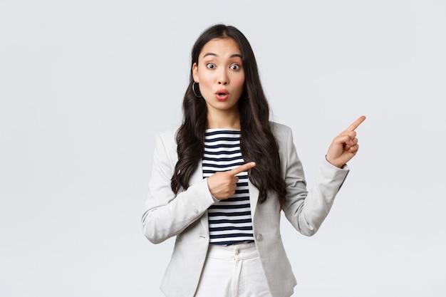Affari, finanza e occupazione, concetto di imprenditrici di successo femminile. donna d'affari incuriosita, agente immobiliare asiatico che punta le dita a destra e che sembra curioso, trova un buon affare Foto Premium