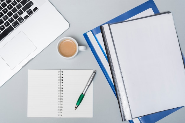 Cartelle aziendali con tazza di caffè; laptop e blocco note a spirale aperta; penna sul tavolo grigio Foto Premium