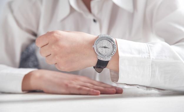 Ragazza di affari che mostra il suo orologio da polso. Foto Premium