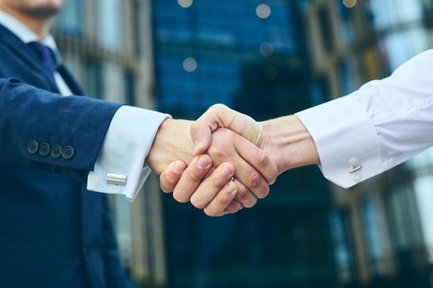 Stretta di mano di affari all'aperto davanti all'edificio per uffici. concetto di riunione di partenariato. handshaking riuscito degli uomini d'affari dopo un buon affare. Foto Premium