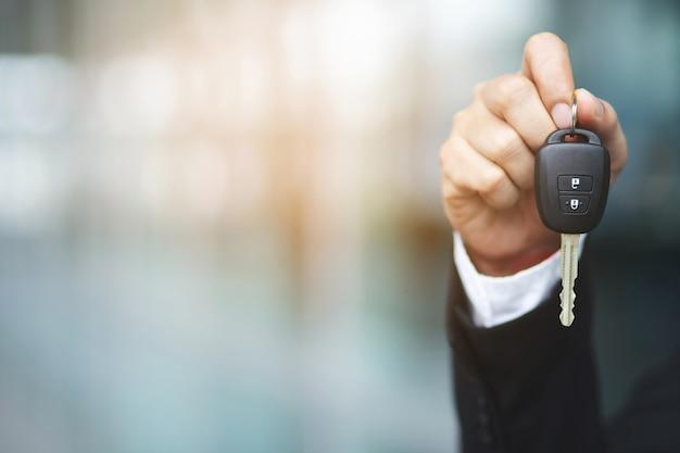 Chiave dell'automobile della holding della mano dell'uomo di affari. concessionaria di trasporto e concetto di vendita Foto Premium