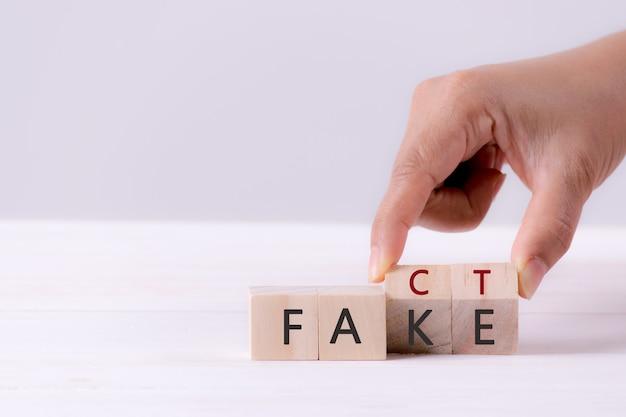 La mano dell'uomo di affari che tiene il cubo di legno con il flip sopra il blocco falsa alla parola di fatto Foto Premium