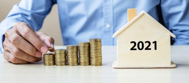 Mano dell'uomo di affari che mette moneta d'oro sulle scale di denaro in crescita con il 2021 Foto Premium