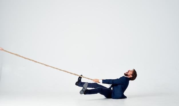 Un uomo d'affari si trova sul pavimento e tira una corda su uno spazio luminoso al chiuso Foto Premium