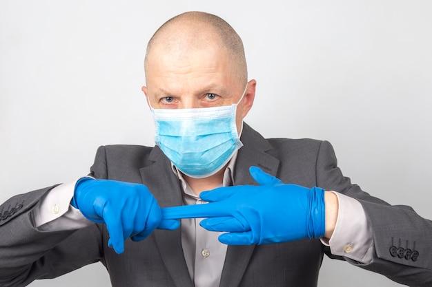 L'uomo d'affari in una mascherina medica si toglie i guanti protettivi dalle mani. quarantena del virus Foto Premium
