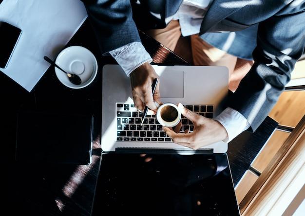 Uomo di affari che si siede in un caffè davanti a uno stile di vita di tecnologia di vista superiore esecutiva della tazza di caffè dei documenti del computer portatile. foto di alta qualità Foto Premium