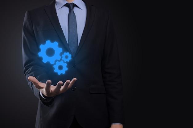 Uomo di affari in vestito che tiene gli ingranaggi del metallo e il meccanismo delle ruote dentate che rappresentano l'interazione Foto Premium