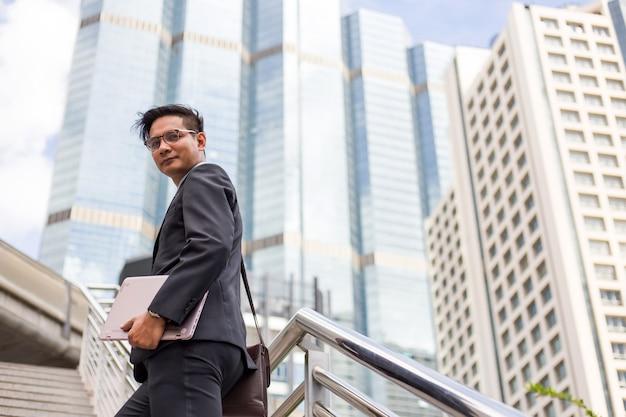 Uomo d'affari con il suo laptop salendo le scale in un'ora di punta per lavorare. tempo di fretta. Foto Premium