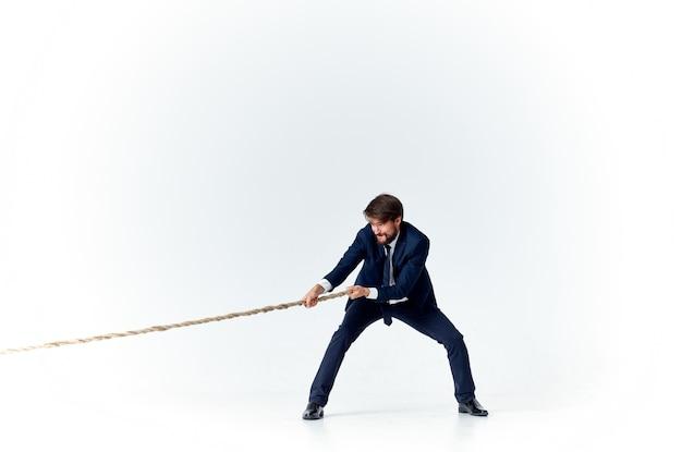Uomo d'affari con una corda in mano su un modello di tensione di sfondo chiaro di raggiungere l'obiettivo Foto Premium