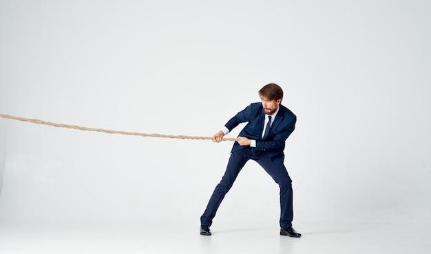 Uomo d'affari con una corda nelle sue mani modello di tensione di raggiungere l'obiettivo Foto Premium