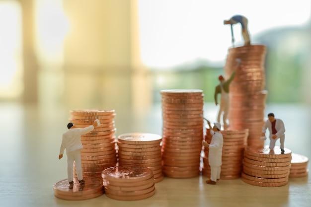 Concetto di affari, denaro, pianificazione e risparmio. chiuda in su del gruppo di pila di pulizia e di verniciatura dell'operaio di moneta. Foto Premium