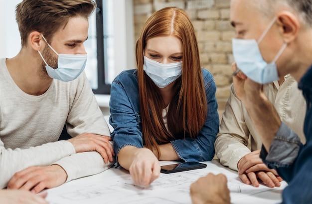 Uomini d'affari che indossano maschere mediche in ufficio Foto Premium