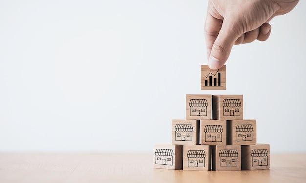 Crescita della vendita aziendale ed espansione del concetto di franchising del negozio, blocco cubo di legno che mette a mano il negozio e il supermercato. Foto Premium