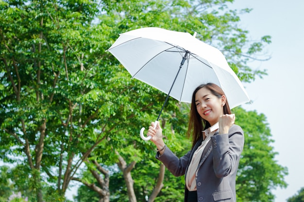 Una donna d'affari che indossa un abito, tiene in mano un ombrello bianco ombreggiato dal sole. e ha alzato una mano felice per lavorare con successo Foto Premium