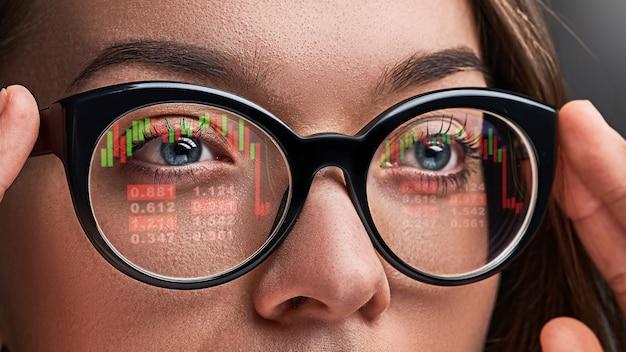 La donna di affari con gli occhiali esamina le quotazioni del mercato azionario e i tassi di cambio durante la crisi finanziaria Foto Premium