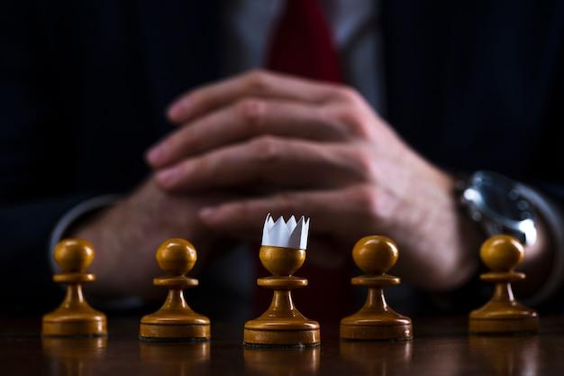 Uomo d'affari a una scacchiera davanti a una pedina con una corona di carta in testa Foto Premium
