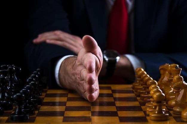 Uomo d'affari alla scacchiera, mano separa pezzi bianchi e neri Foto Premium