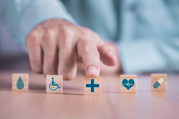 L'uomo d'affari sceglie un simbolo medico sanitario delle icone di emoticon sul concetto di blocco di legno, assistenza sanitaria e assicurazione medica Foto Premium