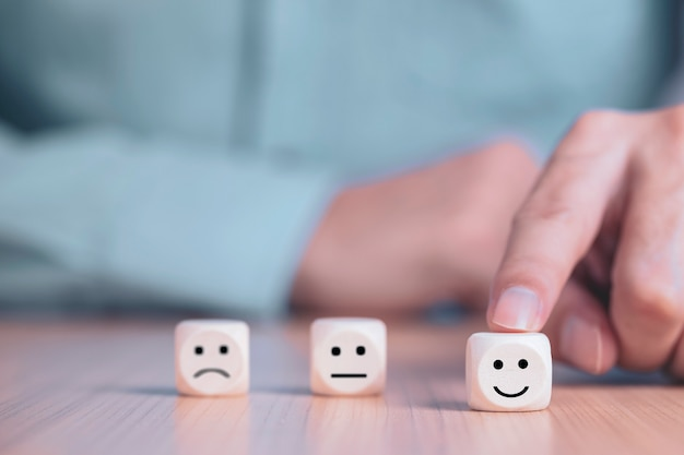 L'uomo d'affari sceglie un fronte di sorriso felice sul blocco di legno Foto Premium