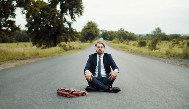 Uomo d'affari in abito classico seduto in mezzo alla strada e meditando con gli occhi chiusi Foto Premium