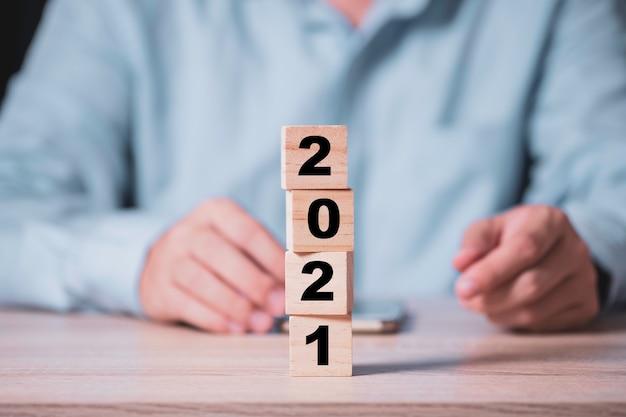 Uomo d'affari che lancia il blocco di cubi di legno per cambiare il 2020 al 2021 anno sul tavolo di legno. felice anno nuovo e inizia un nuovo concetto di business. Foto Premium