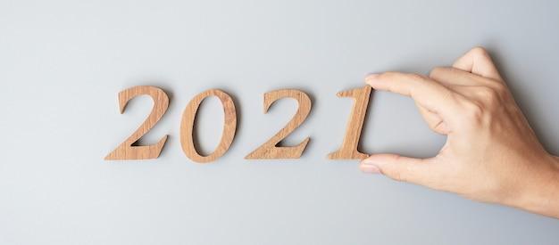 Mano dell'uomo d'affari cambia il numero di legno dal 2020 al 2021 Foto Premium