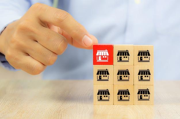 Mano di uomo d'affari sceglie blog di giocattoli in legno di colore reg impilati con negozio di icone di marketing in franchising. Foto Premium