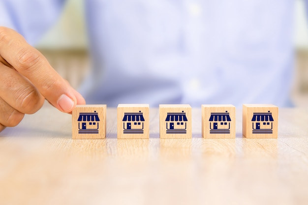 Mano dell'uomo d'affari sceglie il posto di legno del blog in linea con il negozio di icone di marketing in franchising Foto Premium