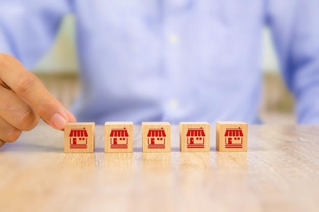 Mano di uomo d'affari sceglie blog in legno con negozio di icone di marketing in franchising Foto Premium