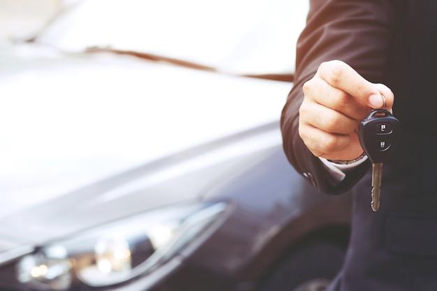 Mano di uomo d'affari che tiene le chiavi della macchina davanti con auto nuove, parcheggio davanti alla casa. concetto di trasporto. Foto Premium