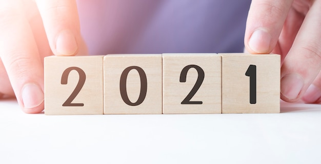 Mano di uomo d'affari che tiene blocco cubo di legno con 2021 parola d'affari sul tavolo Foto Premium