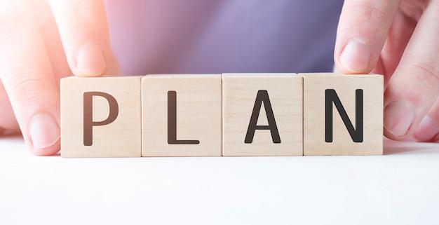 Mano di uomo d'affari che tiene il cubo di legno con blocco parola di affari di piano sul fondo della tabella. missione, visione e concetto di valori fondamentali Foto Premium
