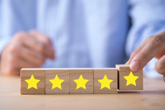Mano dell'uomo d'affari che mette stella gialla che è stampata sul cubo di legno. sondaggio sulla valutazione del cliente e concetto di soddisfazione. Foto Premium