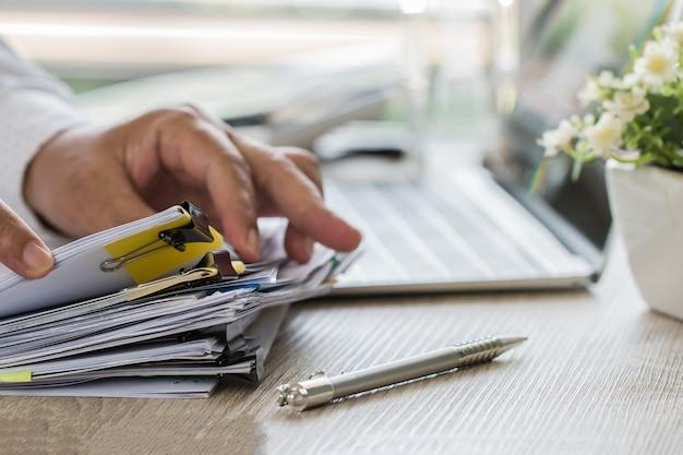 L'uomo d'affari passa la penna di tenuta per il lavoro nelle pile di archivi cartacei che cercano la relazione di attività di informazioni Foto Premium