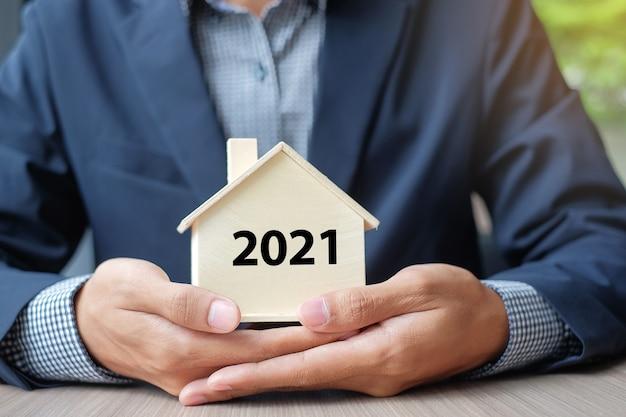 Mani dell'uomo d'affari che tengono il modello di casa in legno con il 2021 Foto Premium