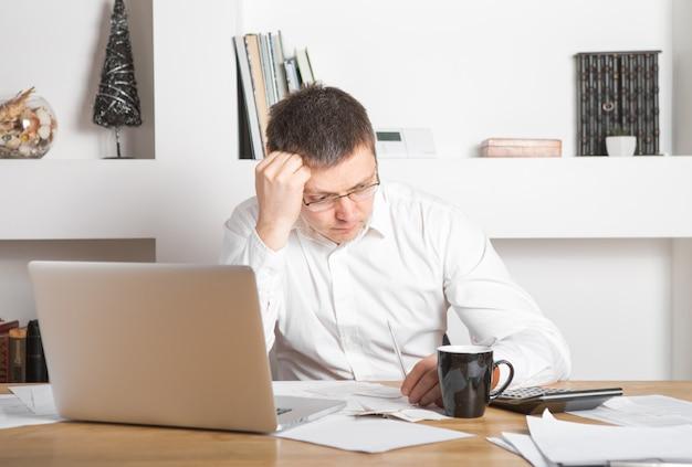 Uomo d'affari che ha sforzo con il computer portatile che lavora nell'ufficio, uomo caucasico che tocca la sua testa, sta avendo un mal di testa, uno sforzo e un concetto di lavoro eccessivo. Foto Premium