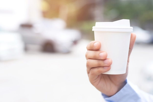 Un uomo d'affari con in mano una tazza di caffè caldo, ha bevuto il caffè prima di guidare. Foto Premium