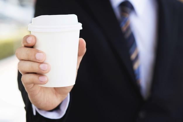 Un uomo d'affari che tiene una tazza di caffè calda, ha bevuto il caffè prima del lavoro la mattina Foto Premium
