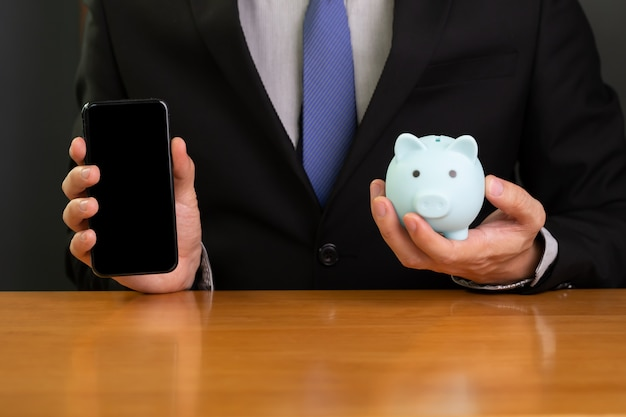 Uomo d'affari che tiene telefono cellulare e salvadanaio. Foto Premium