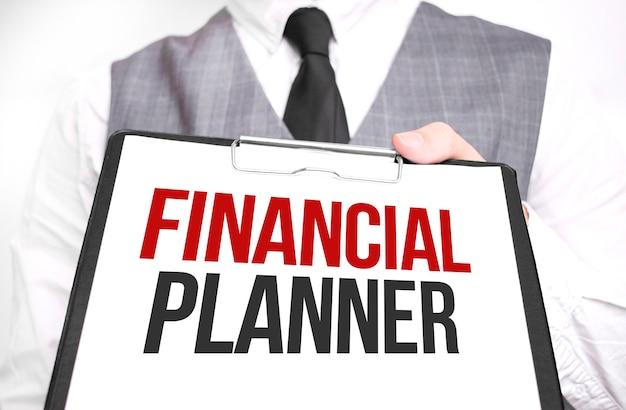 Uomo d'affari che tiene foglio di carta con un messaggio pianificatore finanziario Foto Premium