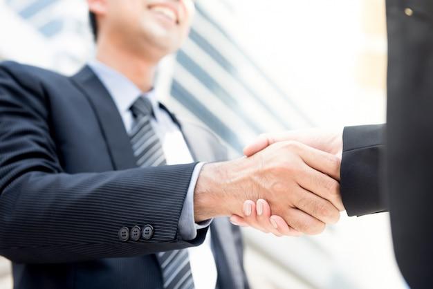 Uomo d'affari che fa stretta di mano con una donna di affari Foto Premium