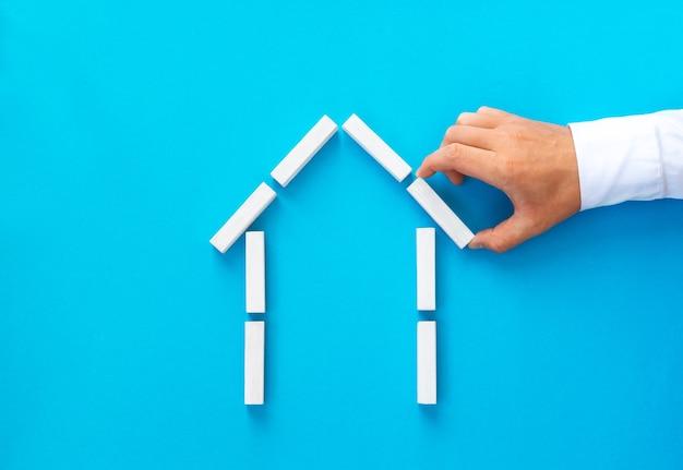 Uomo d'affari che fa una casa di blocchi di legno Foto Premium