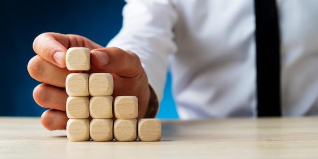 Uomo d'affari che mette i dadi di legno in bianco in una scala come la struttura in un'immagine concettuale. Foto Premium