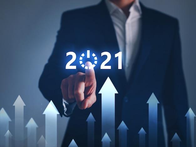 Uomo d'affari che indica il pulsante futuro start dell'anno 2021 con grafico digitale. Foto Premium